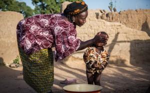 Hawa washes her one-year-old son Roukiatou at home, Nabitenga, Burkina Faso.