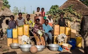 Hawa with her family and livestock, and the water containers she must fill every day.